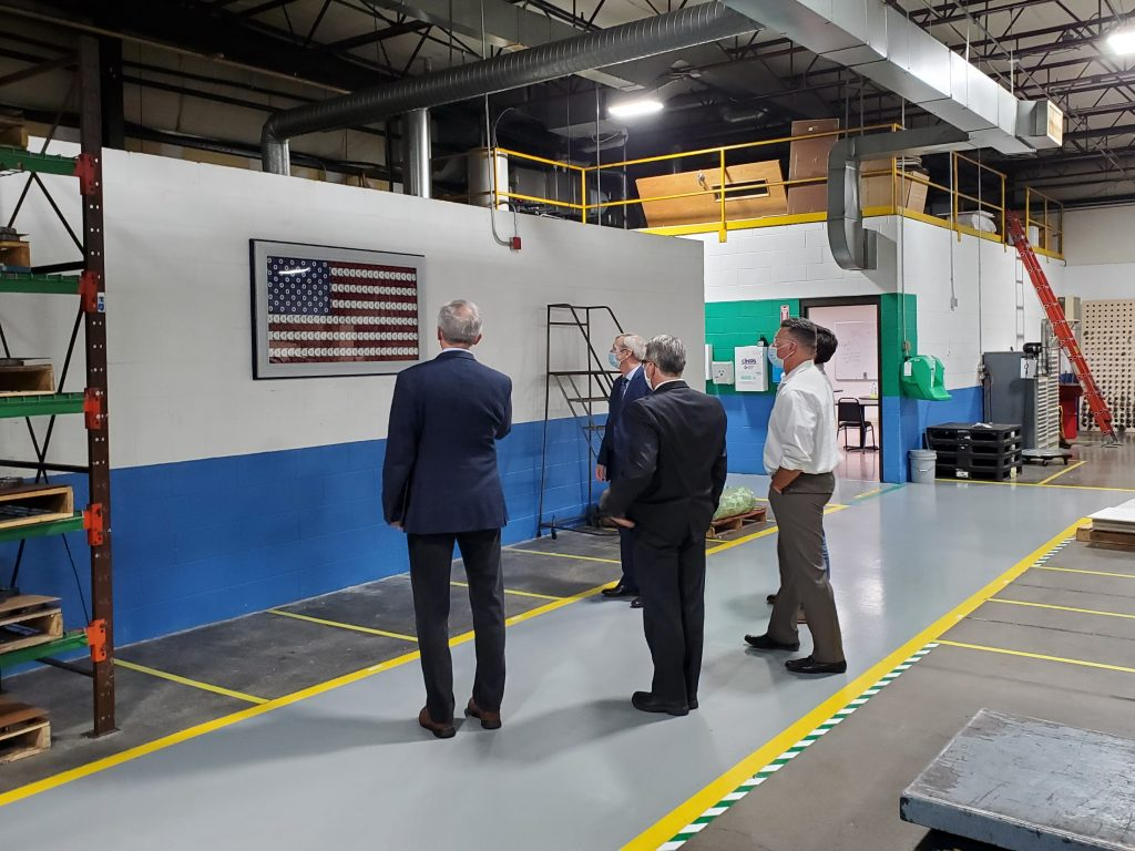 John Katko and Randy Wolken admire the American flag made from gears displayed on the shop floor at Nixon Gear