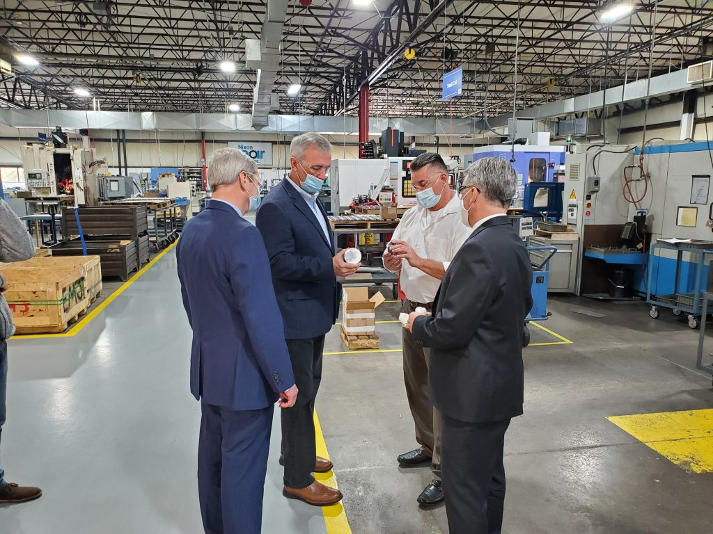Dean Burrows and Dan Bartelli explain the gear manufacturing process to John Katko and Randy Wolken during a tour of Nixon Gear's manufacturing facility