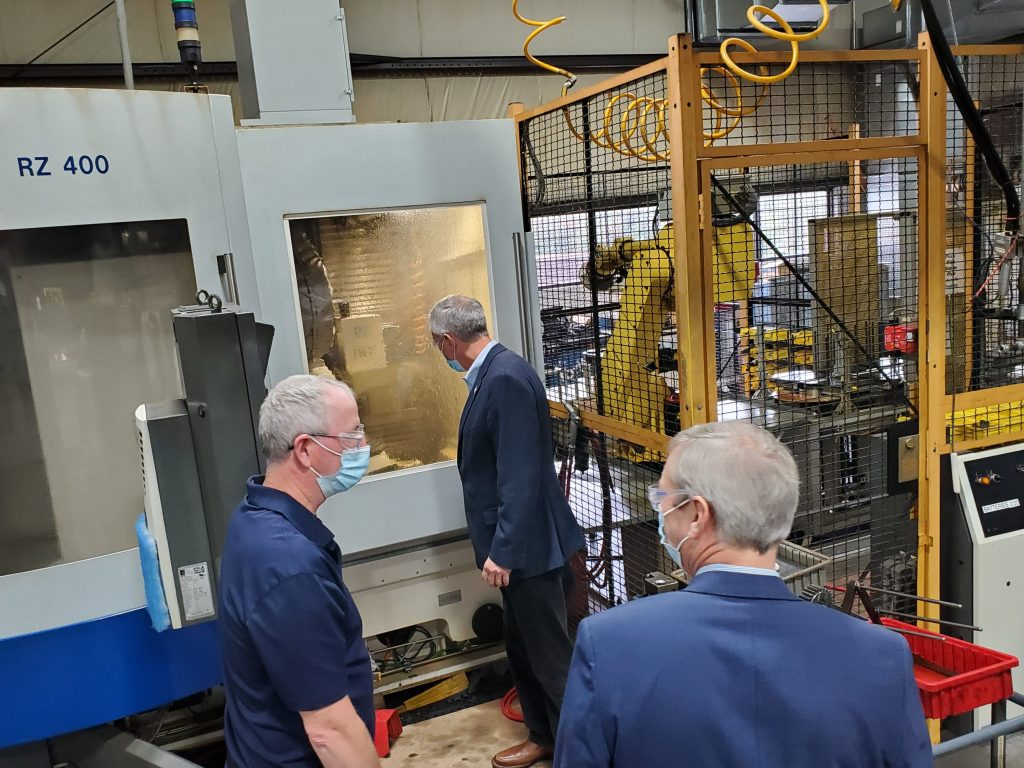John Katko observes a gear grinding machine in action during a tour of Nixon Gear's manufacturing facility